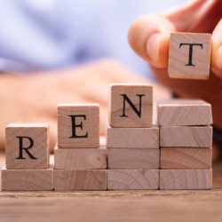 Multifamily Rent Increase With Hand Stacking Alphabet Blocks Higher