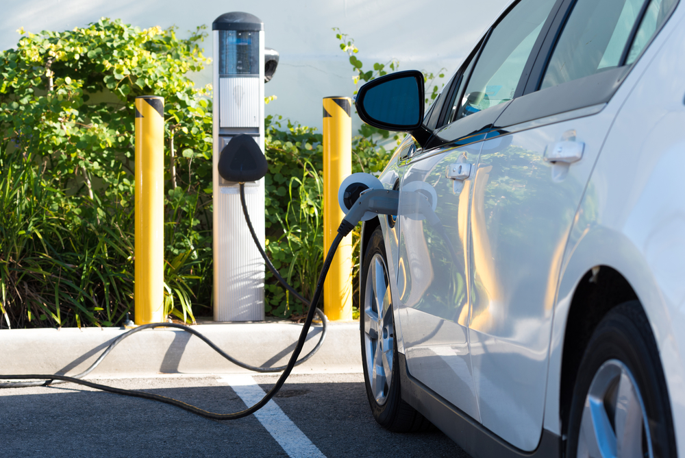 Electric Car Charging At EV Charging In Retail Parking Lot