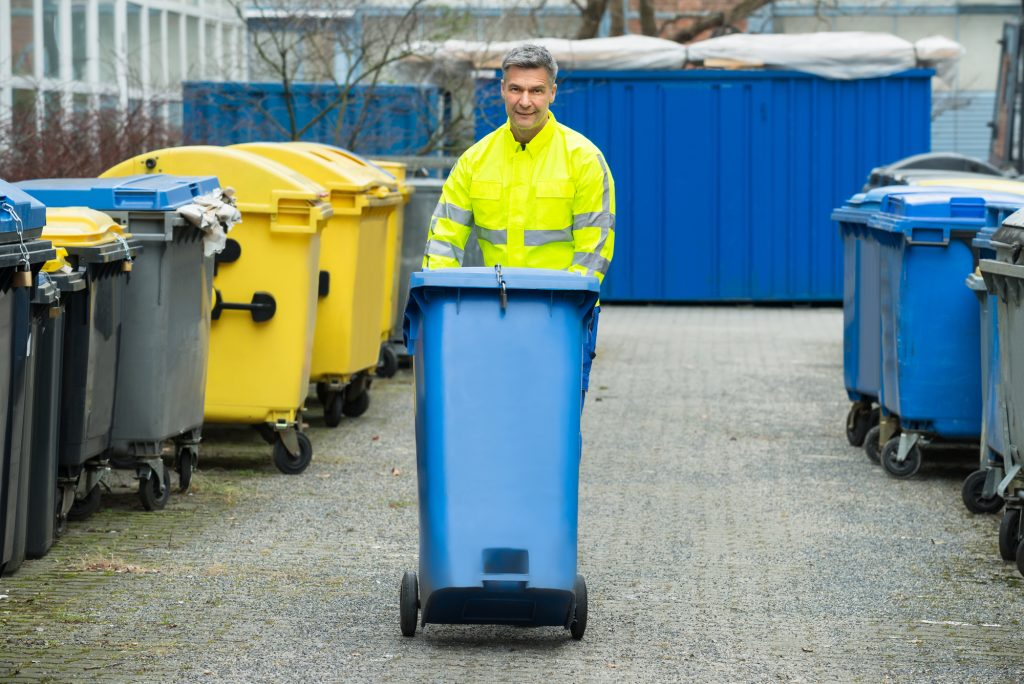 Valet Trash Company Employee Walking Bin In Dumpster Area For A Brief Overview of Valet Trash Services Blog