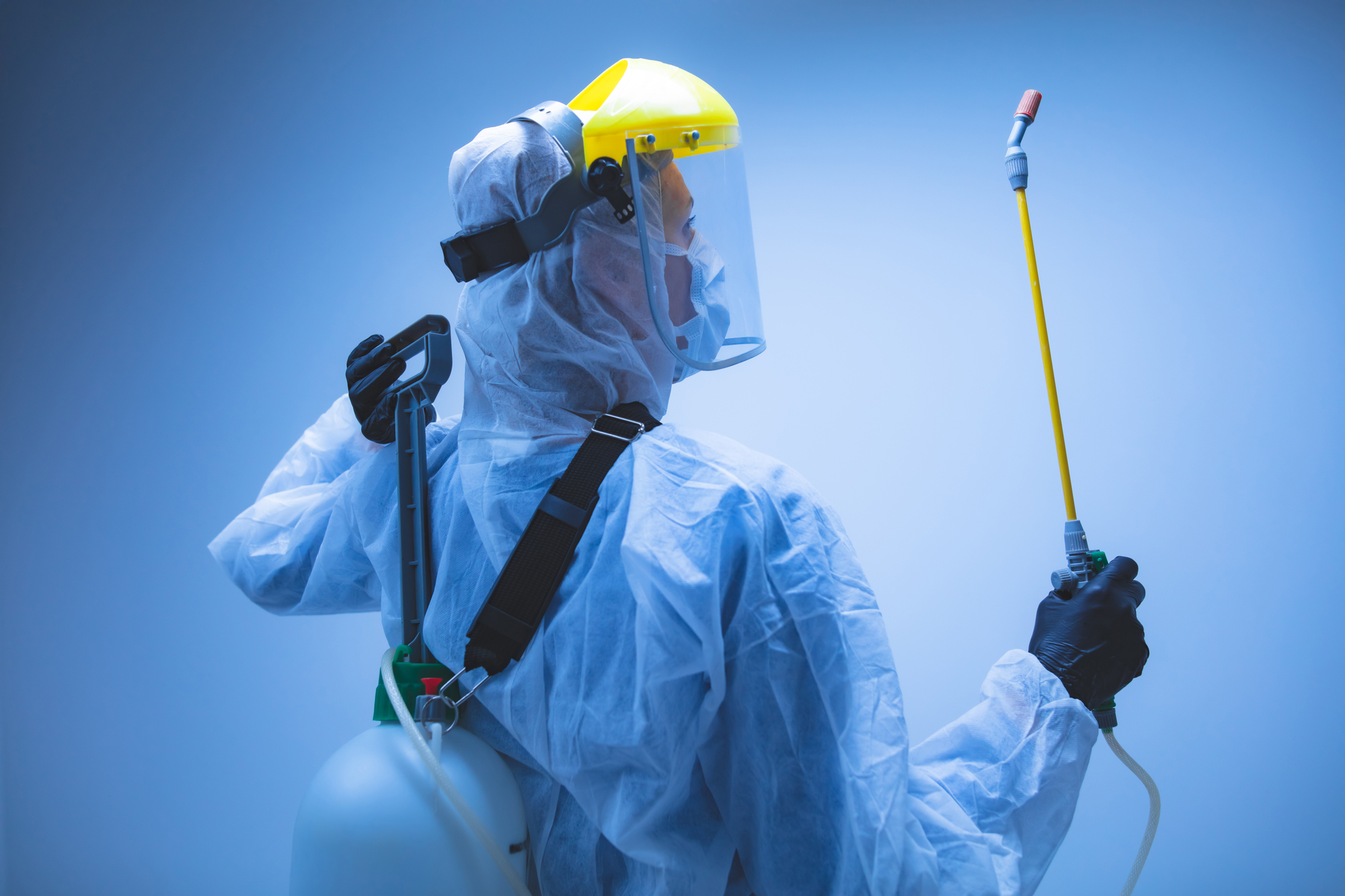 Commercial Cleaner In Hazmat Suit Disinfecting Commercial Office Buildings Against CoronaVirus With Chemical Sprayer