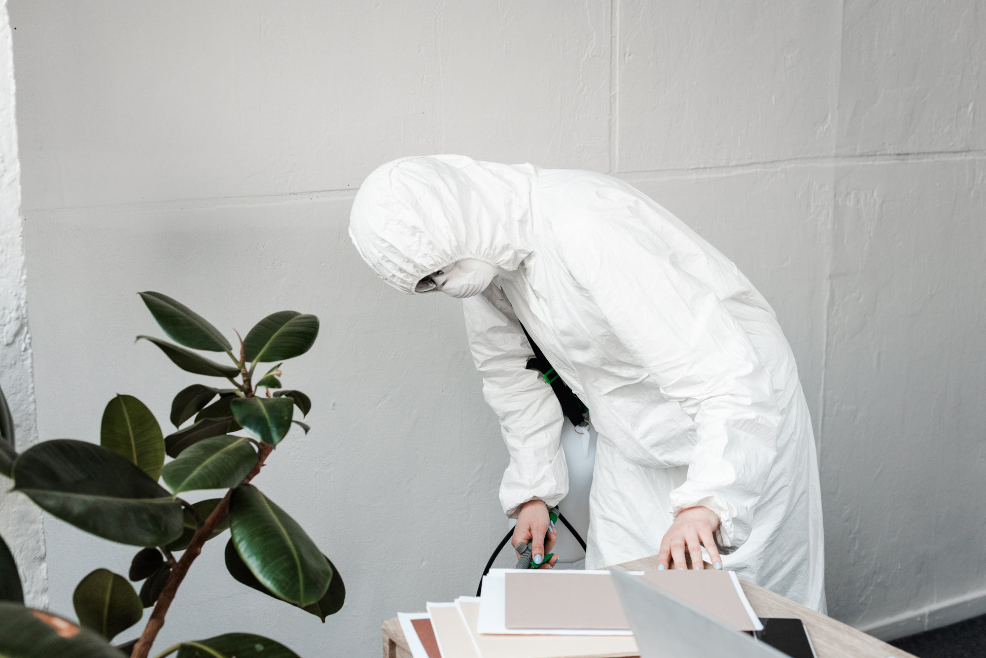 Man in Hazmat Suit Disinfecting Office Showing The Benefits of Electrostatic Disinfecting